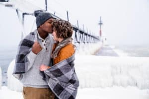 Interracial couple during a snowy engagement session in michigan
